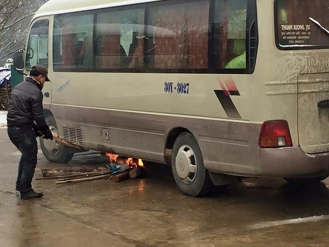 Không chỉ xe tải, xe khách Hyundai loại 29 chỗ này cũng chết máy vì lạnh. Tài xế này đang vô tư đốt lửa để sưởi cho bình nhiên liệu (Nguồn: Fb Trung Anh)