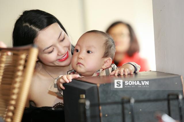 Ngồi trong lòng mẹ, bé Su Hào vẫn hướng mắt về phía bố.