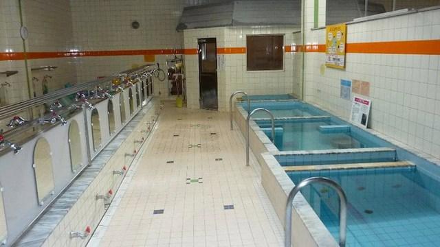Thiết kế đặc trưng của một nhà tắm công cộng với hàng vòi nước dài bên cạnh bể nước nóng.