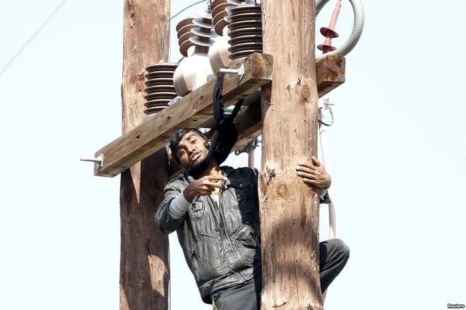 Một người di cư dọa treo cổ tự tử trên cột điện trong cuộc biểu tình tại trung tâm đăng ký tị nạn Moria ở Lesbos, Hi Lạp.