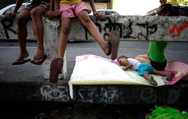 Em bé ngủ ngay trên cầu tại một khu ổ chuột ở thành phố Manila, Philippines.