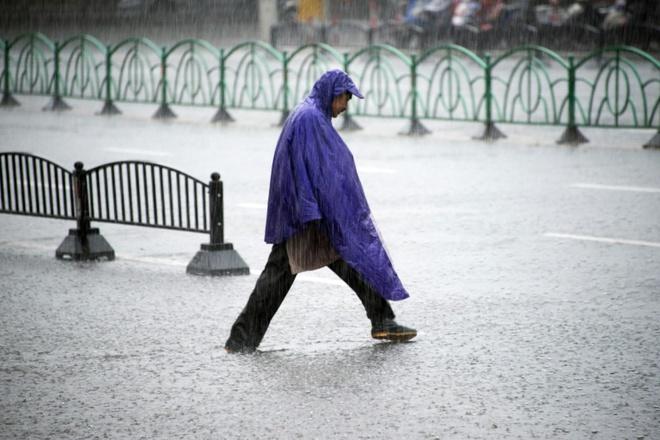 Người đàn ông qua đường dưới trời mưa lớn ở Thượng Hải, Trung Quốc.