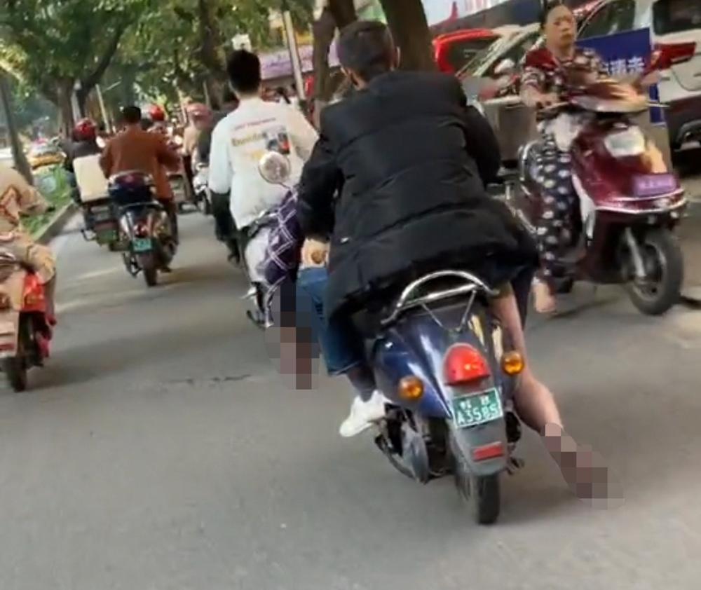 Người đàn ông điều khiển xe máy chở thi thể ngay trên đường phố, chân người chết bị kéo lê suốt dọc đường - Ảnh 2.