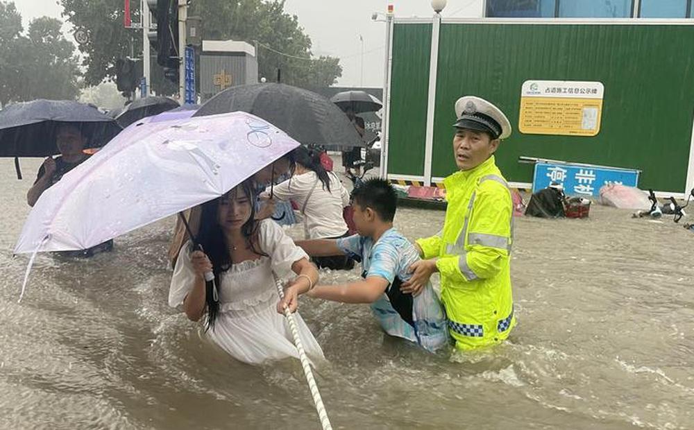 24h qua ảnh: Người dân Trung Quốc dùng dây vượt qua đường phố ngập lụt