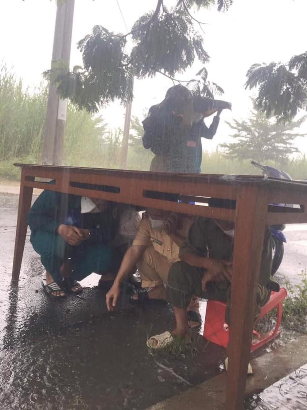 CSGT và đội trực chốt kiểm dịch nép dưới gầm bàn trú mưa, nhìn xuống đôi dép lại càng thêm xót xa - Ảnh 1.