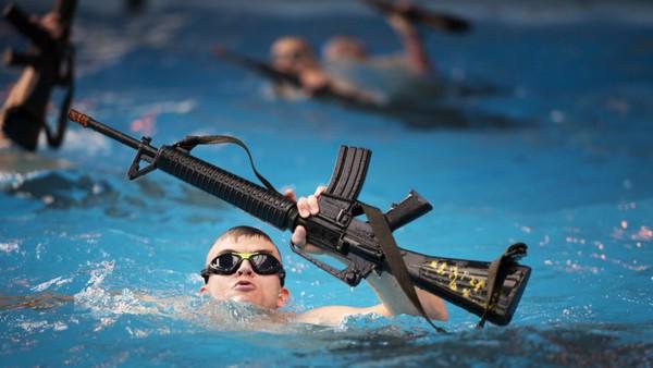 Các binh sĩ vừa bởi vừa phải giữ khẩu súng trường cao su có trọng lượng tương tự khẩu M-16 đã nạp đạn không bị ướt.