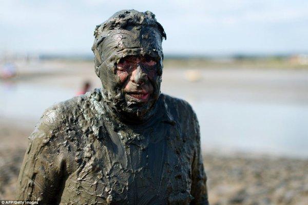Một người đàn ông với bùn bao phủ từ chân tới đầu.