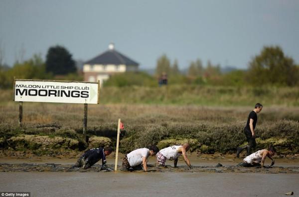 Những người dự thi khó nhọc bò trên bùn.