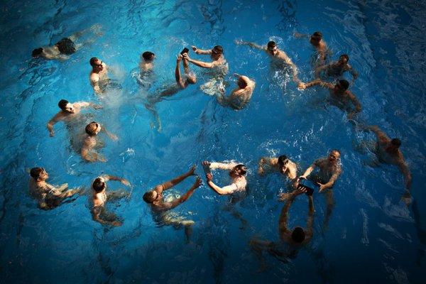 Luyện tập kỹ năng vừa bơi vừa truyền gạch qua đầu trên mặt nước.