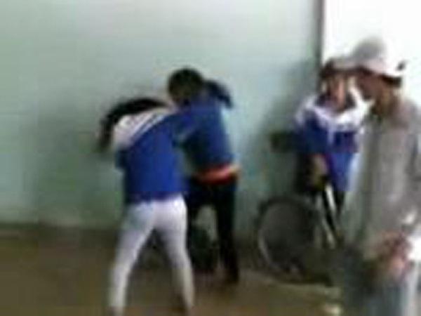 Hai nữ sinh vừa đánh nhau vừa văng ra những lời tục tĩu trong khi những học sinh khác đứng ngoài cổ vũ là học sinh Trường THPT Đinh Chương Dương (ảnh cắt từ video).