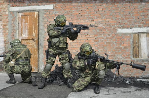 Trong khi đó một lính đặc nhiệm khác (ở giữa) lại được trang bị súng trường tấn công AK với ống phóng lựu và hộp tiếp đạn tròn loại 100 viên.