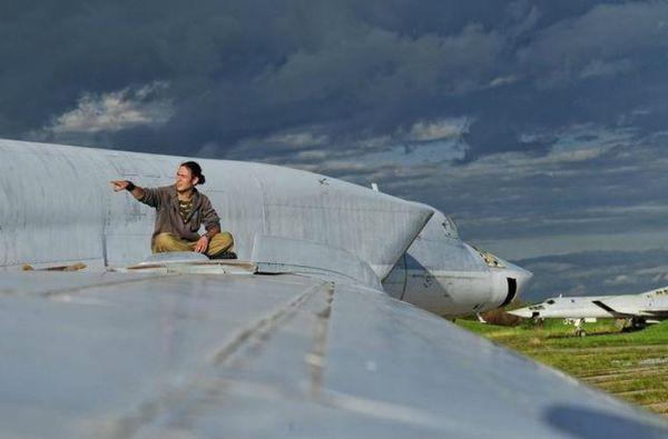 Một trong những nhóm người lọt vào căn cứ bỏ hoang đang ngồi trên cánh chiếc Tu-22M.