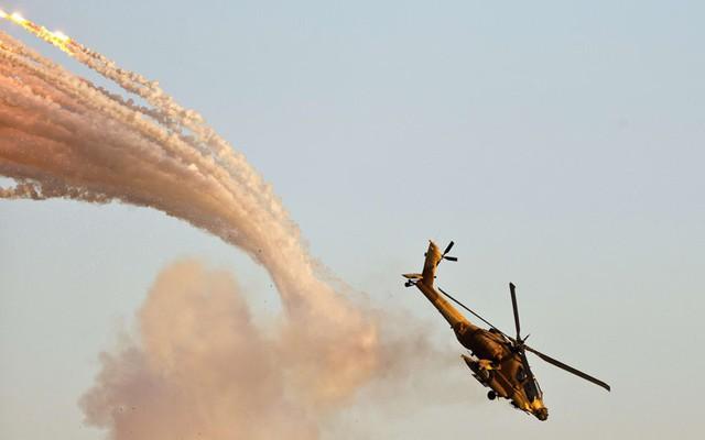 Một chiếc trực thăng tấn công Boeing AH-64 Apache Longbow phóng pháo sáng chống tên lửa trên bầu trời trong lễ tốt nghiệp của phi công tại căn cứ quân sự Hatzerim trên sa mạc Negev của Israel.