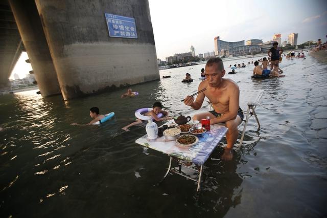 Một người đàn ông vừa ngâm chân dưới nước vừa ăn tối trên bờ sông Hàn Giang ở Vũ Hán, Trung Quốc, khi nắng nóng ở đây đang ở mức kỷ lục.