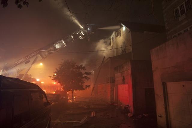 Lính cứu hỏa đang tiến hành dập tắt lửa trong một ngôi nhà bị hỏa hoạn tại thành phố New York, Mỹ.