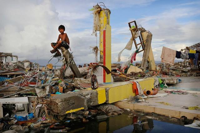 Cậu bé ngồi trên đống đổ nát của một tòa nhà bị tàn phá bởi siêu bão Haiyan tại thành phố Tacloban, Philippines.