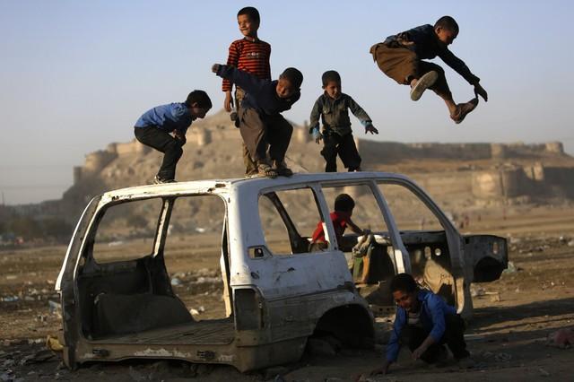 Trẻ em chơi đùa trên một chiếc xe ô tô hỏng ở Kabul, Afghanistan.