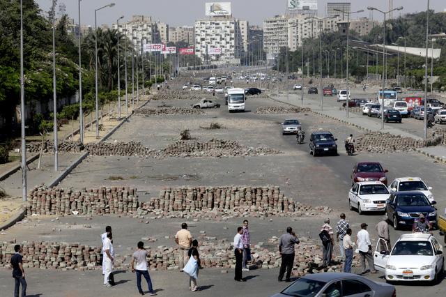Mọi người đi các qua hàng rào chắn được làm gạch trên đường phố dẫn tới nhà thờ Rabaah al-Adawiya, nơi những người ủng hộ cựu Tổng thống Mohammed Morsi đang tổ chức biểu tình ở Cairo, Ai Cập.