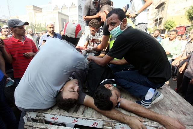 Những người biểu tình sơ cứu cho những đồng đội bị thương trong cuộc đụng độ với cảnh chống bạo động gần quảng trường Ramses, Cairo, Ai Cập.