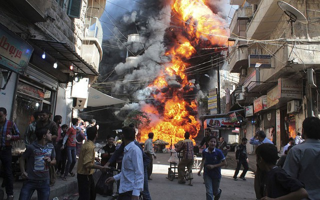 Người dân nhìn lửa bốc lên nghi ngút từ một cửa hàng xăng dầu ở Aleppo, Syria.