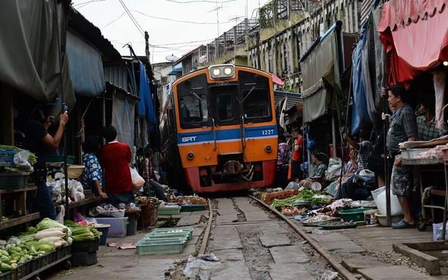 Tàu hỏa đi qua một chợ bán thực phẩm ở Maeklong, gần thủ đô Bangkok của Thái Lan.