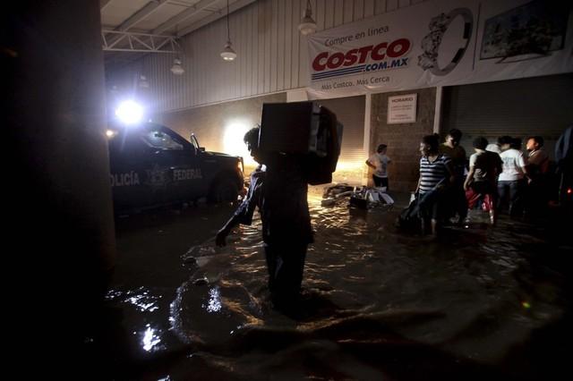 Mọi người vác hàng hóa lội trên đường phố ngập lụt ở Acapulco, Mexico.