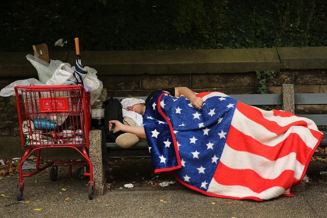 Một người vô gia đắp tấm chăn in lá cờ Mỹ trong khi đang ngủ trên ghế tại một công viên ở New York, Mỹ.