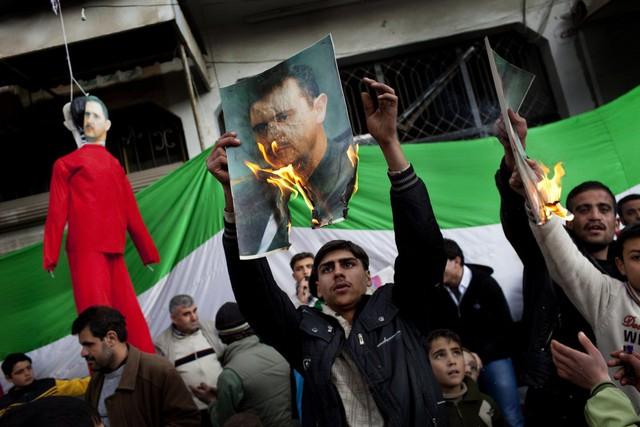 Mọi người đốt ảnh chân dung của Tổng thống Assad trong cuộc biểu tình ở Idlib, Syria, ngày 26/2/2012.