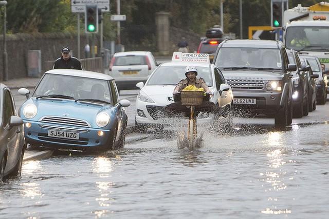 Một người đi xe đạp cố gắng vượt qua đoạn đường ngập lụt ở Glasgow, Scotland.