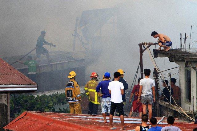 Lính cứu hỏa và người dân nỗ lực dập tắt đám cháy tại một khu ổ chuột ở thành phố Malabon, Philippines.