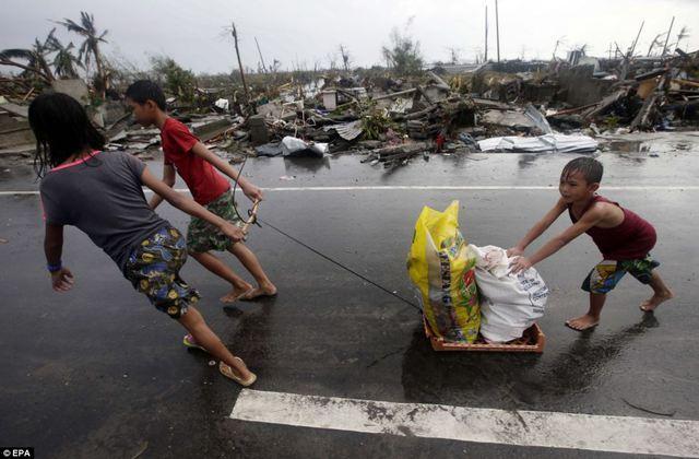 Trẻ em kéo những bao tải thực phầm và hàng hóa lấy được từ các cửa hàng vô chủ.