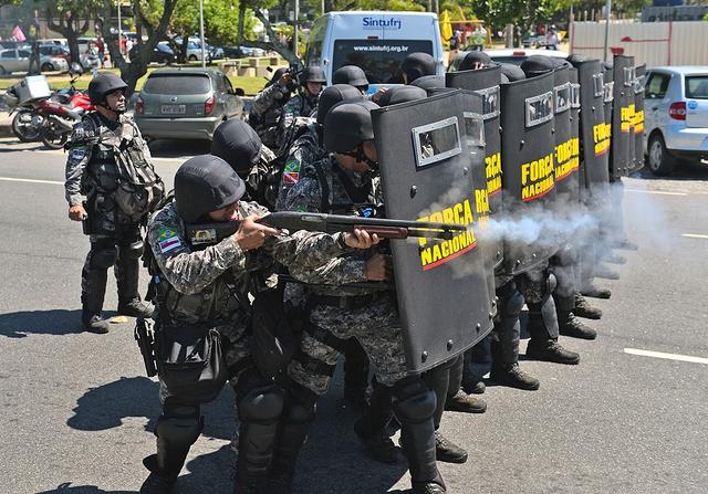 Lực lượng an ninh quốc gia Brazil bắn đạn hơi cay vào những người biểu tình trước một khách sạn ở Rio de Janeiro.