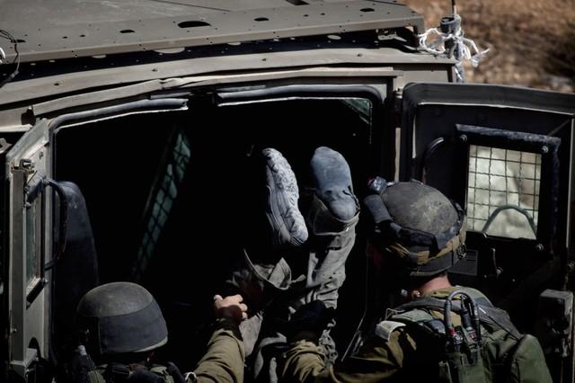 Binh sĩ Israel đưa thi thể một phiến quân Hồi giáo vũ trang bị bắn hạ vào xe ô tô ở thành phố Ramallah, Bờ Tây.