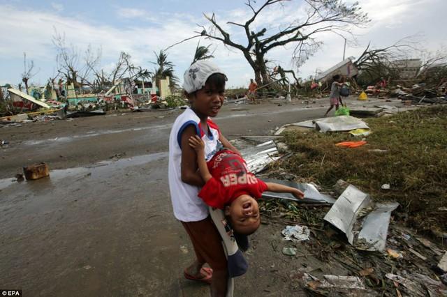 Một cậu bé vất vả bế em đang khóc giữa khung cảnh hoang tàn ở thành phố Tacloban.