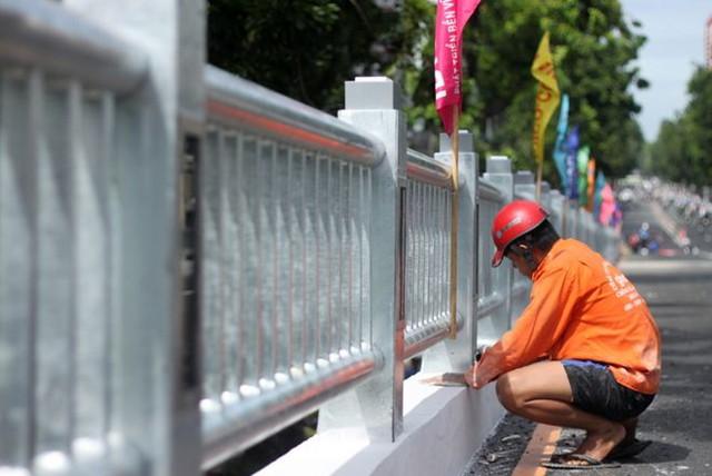 Các công nhân gấp rút hoàn thành những công đoạn cuối như sơn cầu, lắp biển báo...