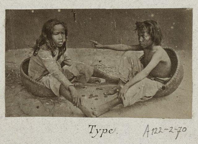 Hai đứa trẻ làm bốc vác tại bến cảng đang chơi bên cạnh những đồng xu hiếm hoi.