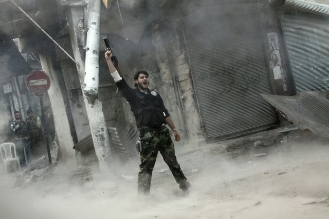 Một chiến binh của lực lượng phiến quân ăn mừng chiến thắng sau khi phóng tên lửa vác vai trúng vào quân đội trung thành với Tổng thống Assad ở Aleppo, Syria, ngày 4/11/2012.