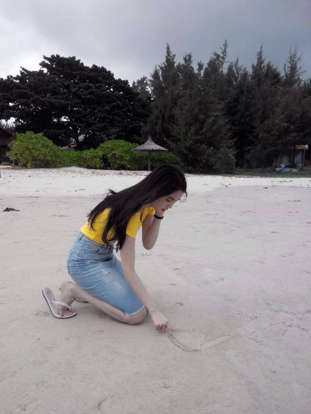 'Nữ hoàng nội y' cặm cụi viết tên mình trên cát