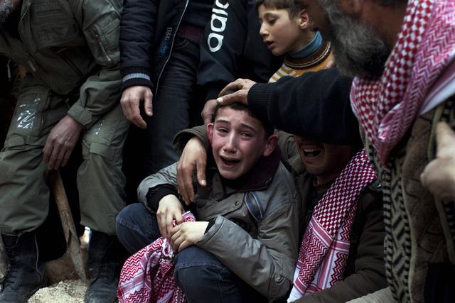 Cậu bé Ahmed khóc trong lễ tang của người bố bị lính bắn tỉa của quân đội chính phủ giết chết ở Idlib, Syria, ngày 8/3/2012.