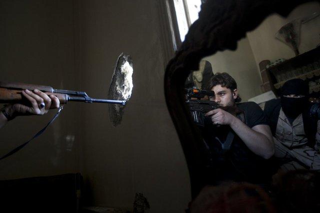 Một lính bắn tía của lực lượng phiến quân chĩa súng vào quân đội chính phủ, trong khi một chiến binh khác phản chiếu qua gương trong một tòa nhà ở quận Jedida của thành phố Aleppo, Syria, vào ngày 29/10/2012.