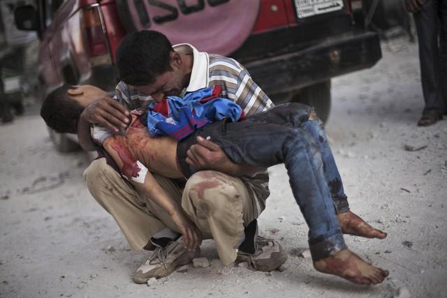 Người đàn ông khóc khi bế cậu con trai gần bệnh viện Dar El Shifa ở Aleppo, Syria, vào ngày 3/10/2012. Cậu bé bị quân đội chính phủ giết hại.