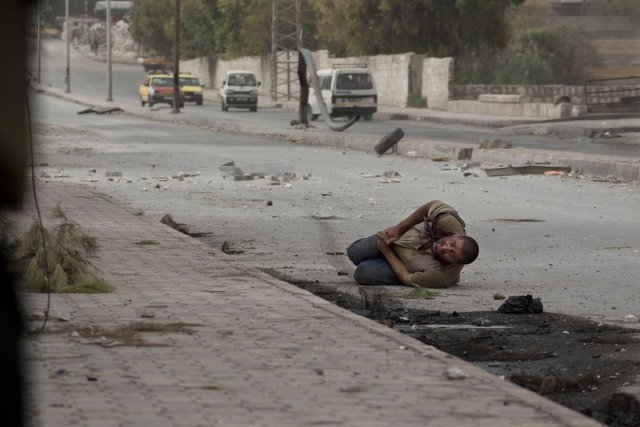 Một người đàn ông nằm trên đường phố sau khi bị trúng đạn từ lính bắn tỉa của quân chính phủ ở Aleppo, Syria, ngày 20/10/2012.