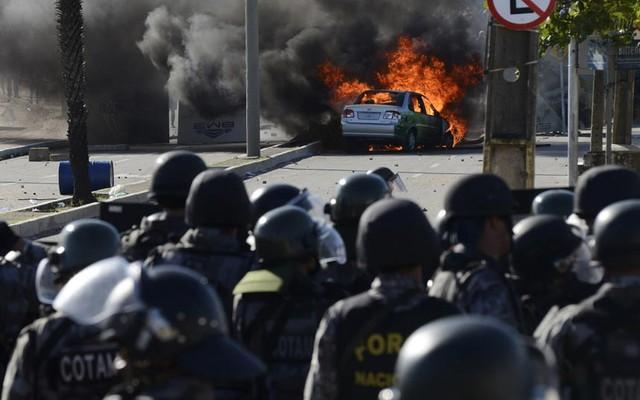 Một chiếc xe bị đốt cháy cạnh cảnh sát chống bạo động trong cuộc biểu tình ở Estadio Castelao, Brazil.