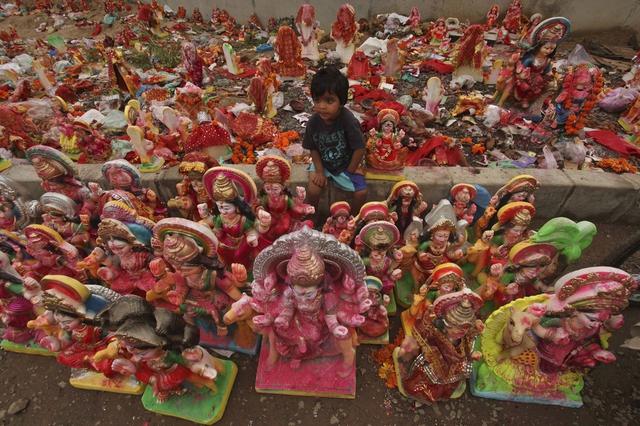 Một cậu bé ngồi giữa những bức tượng thần Dashama của đạo Hindu ở Ahmedabad, Ấn Độ.