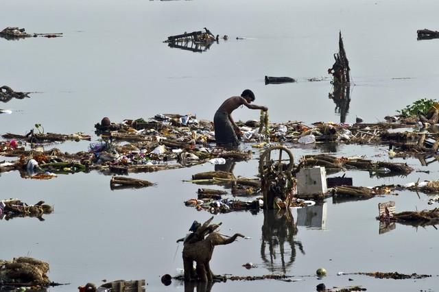 Mọi người bới rác tìm tiền xu và những thứ còn dùng được do những người theo đạo Hindu bỏ lại trên sông Yamuna ở New Delhi, Ấn Độ.