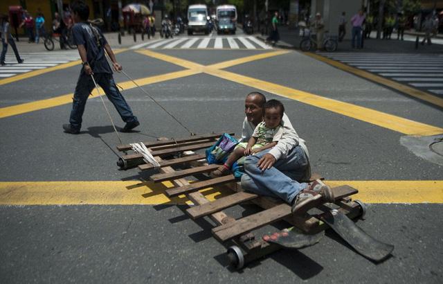 Một cậu bé kéo xe chở bố và em trai trên đường phố ở Medellin, Colombia.