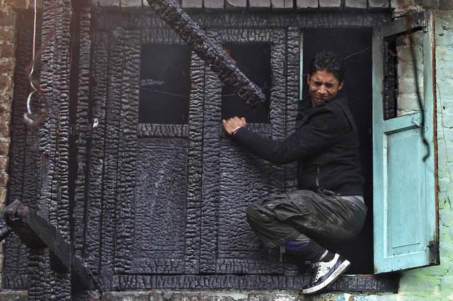 Một người đàn ông cố gắng mở cửa sổ của ngôi nhà bị cháy ở Srinagar, Ấn Độ.