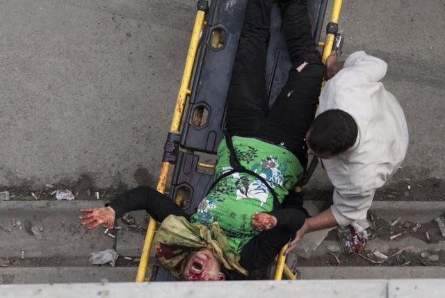 Một người đàn ông đầy một phụ nữ bị thương nặng tới bệnh viện sau khi bị trúng đạn pháo gần một tiệm bánh ở Aleppo, Syria, ngày 23/10/2012.