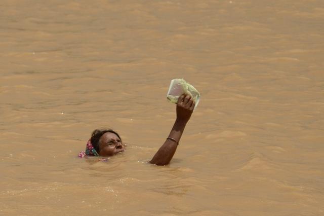 Một phụ nữ cầm một vật trên tay khi cố gắng di chuyển giữ dòng nước lũ ở ngoại ô Patna, Ấn Độ.