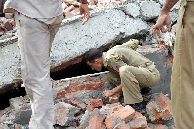 Một cảnh sát tìm kiếm nạn nhân mắc kẹt trong đống đổ nát của một ngôi nhà đang xây dựng bị sập ở Jammu, Ấn Độ.